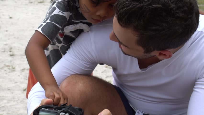 Tourist showing a camera for a Indigenous Children in a Tupi Guarani Tribe, Brazil | Shutterstock HD Video #26220557
