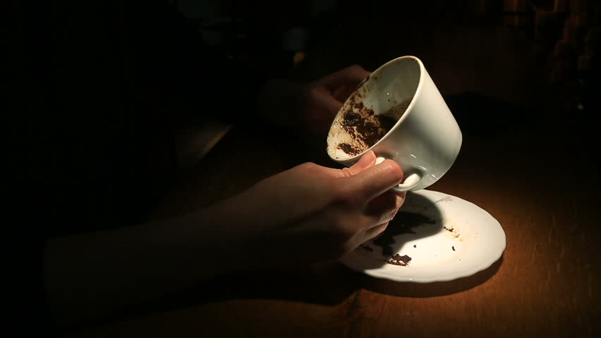 Guessing on the coffee grounds, a female hand holding a coffee mug with coffee grounds. Close-up. | Shutterstock HD Video #26221934