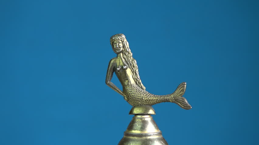 Small vintage brass bell with mermaid sculpture rotating on blue background | Shutterstock HD Video #26230682