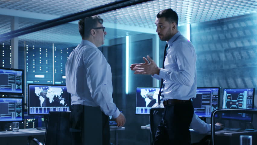 Two IT Engineers Have Discussion and Shake Hands in the Middle of Monitoring Room Full of Working Displays.  Shot on RED EPIC-W 8K Helium Cinema Camera. | Shutterstock HD Video #26262938