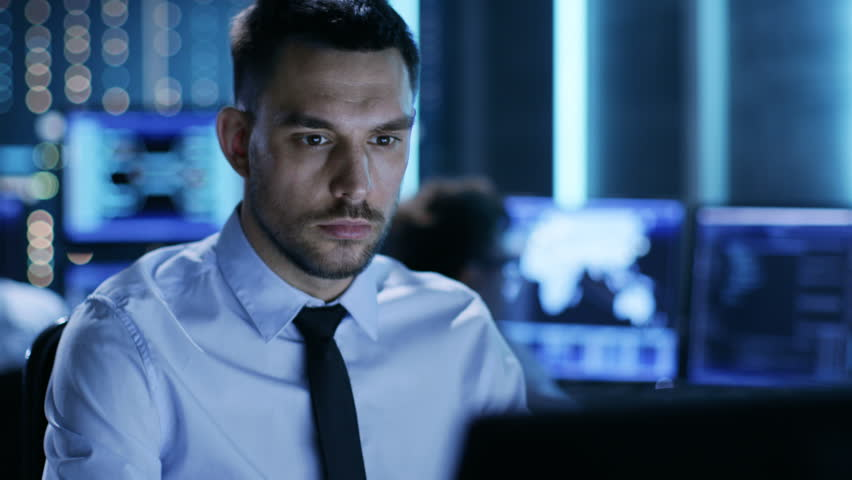 Close-up of a Professional Technical Controller Sitting at His Desk with Multiple Displays Before Him. In the Background His Colleagues Working in System Control Center.  Shot on RED EPIC-W 8K Helium