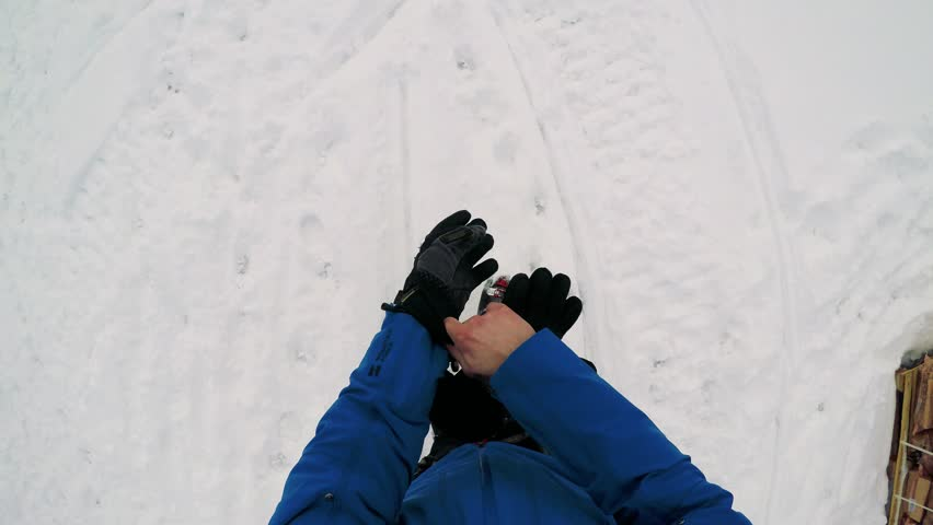 ?NIKKALUOKTA, SWEDEN - APRIL 22, 2017: Man skier walks in winter and he puts on winter gloves - first person view | Shutterstock HD Video #26304302
