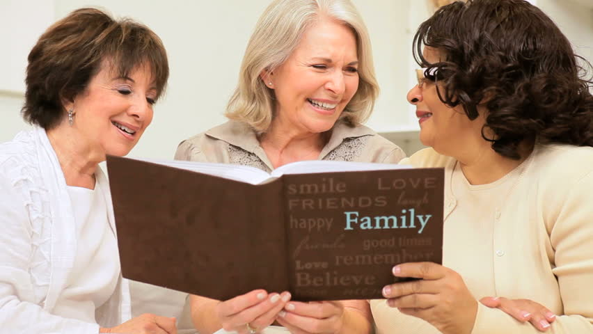 Senior group old friends laughing looking through photo album - HD stock footage clip