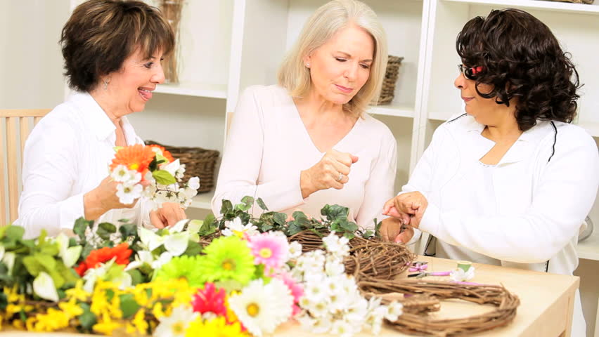 Multi ethnic older female friends crafting silk flowers - HD stock video clip