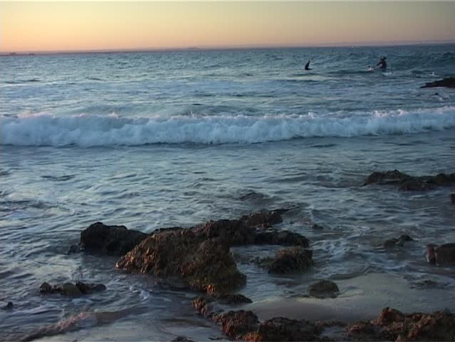 Paddle Skier riding waves at Sunset on the Ocean. - SD stock video clip
