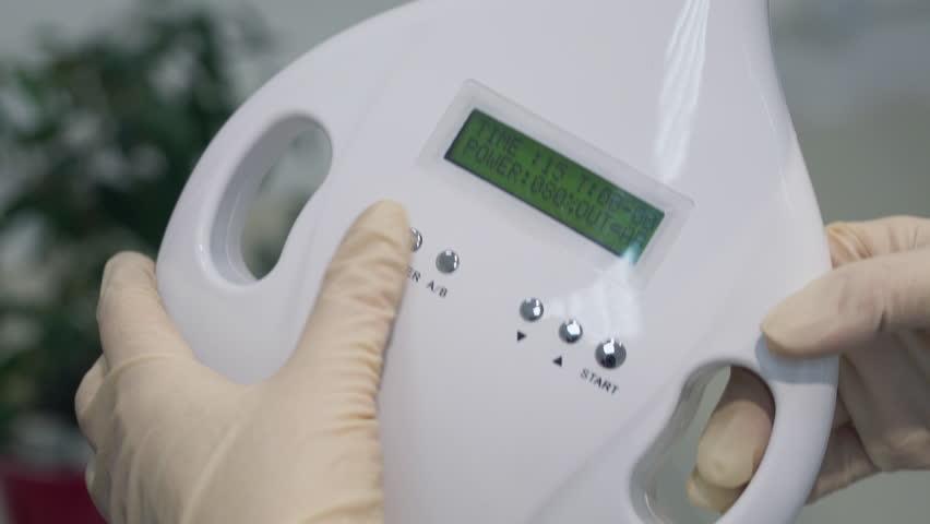 Women's hands in gloves starting a teeth whitening machine, Newest Laser Dental Bleaching. 4K. Close up. | Shutterstock HD Video #26548265