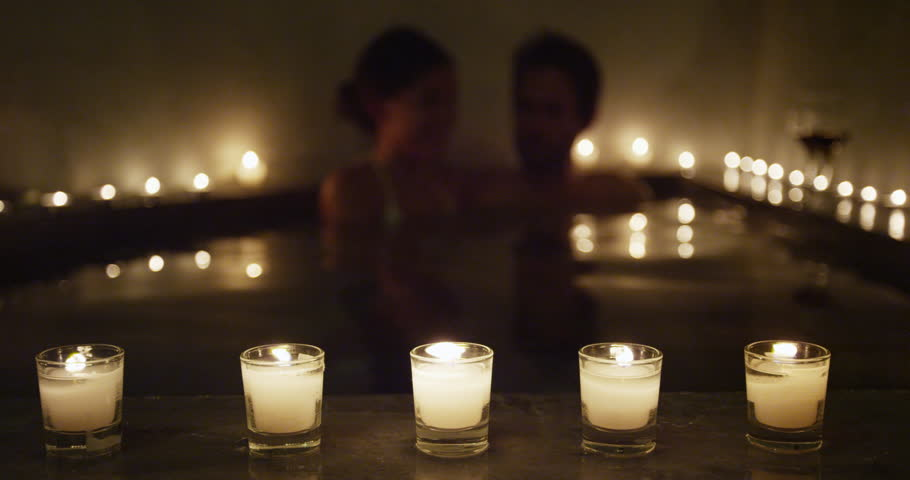 Young couple relaxing in romantic candlelit hot tub jacuzzi spa resort at night in private hotel room terrace. Romantic honeymoon getaway travel vacation adults enjoying their holidays. #26590466