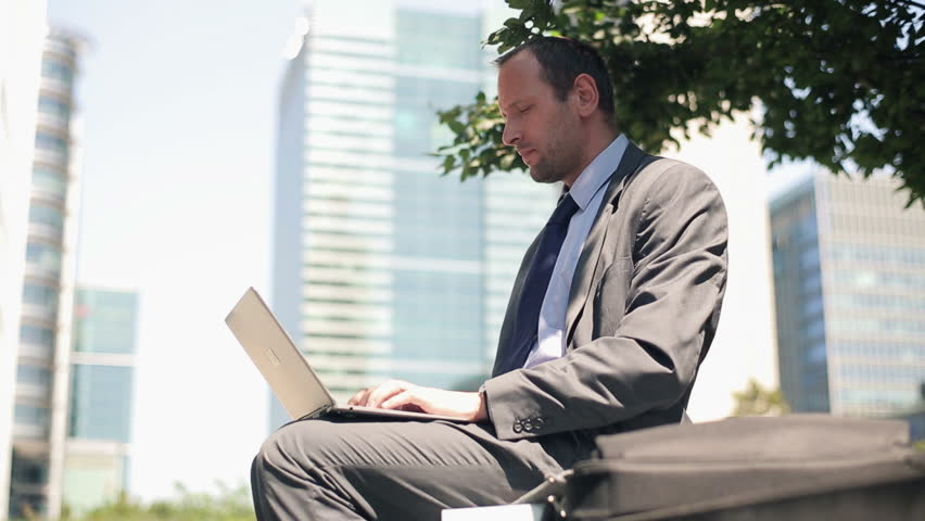 Young handsome businessman working on laptop in the city