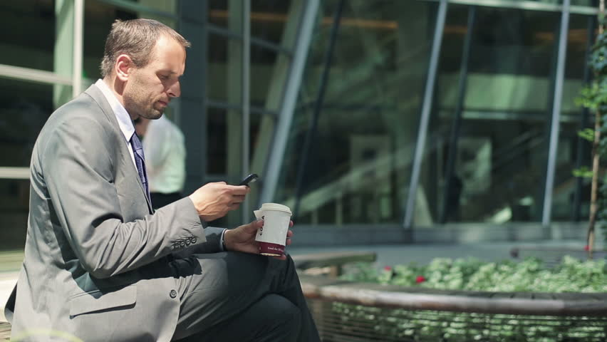 Young businessman drinking coffee and using smartphone in the city