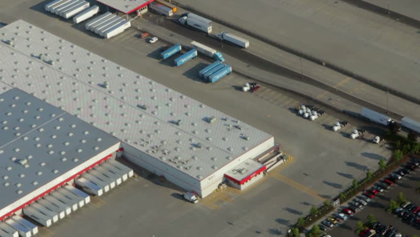 Aerial perspective of cargo transport trucks at large freight hub - HD stock footage clip