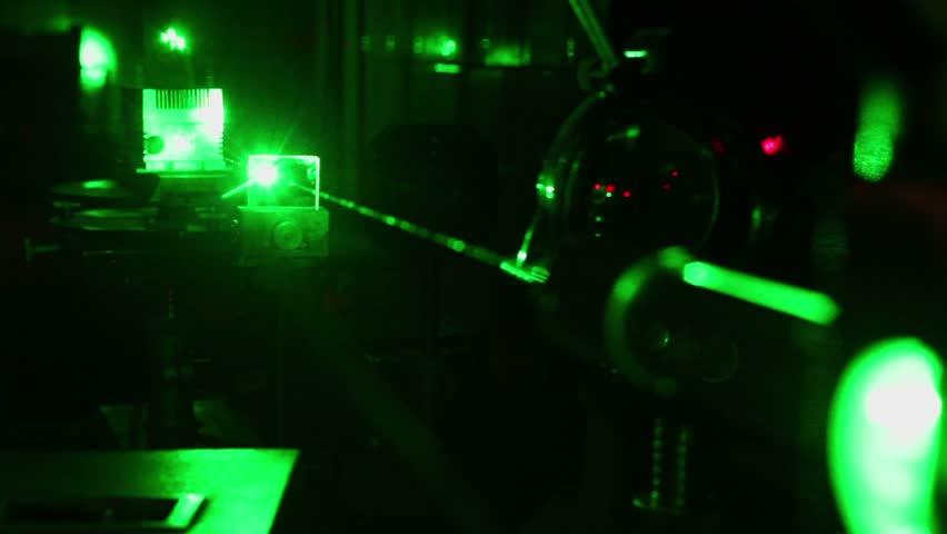 Glisten beam of green laser on table in dark laboratory - HD stock footage clip