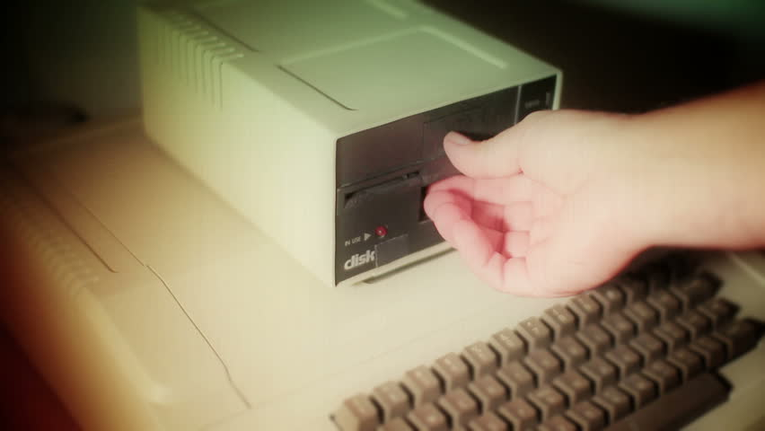 """Old film look treatment of a close-up of inserting and removing an old-style 5.25"""" floppy disk."""