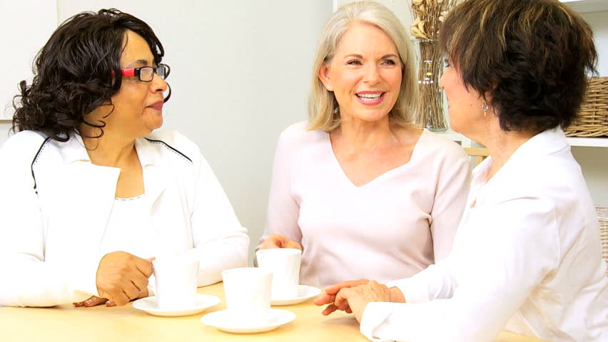 Group older multi ethnic ladies laughing drinking coffee home - HD stock footage clip