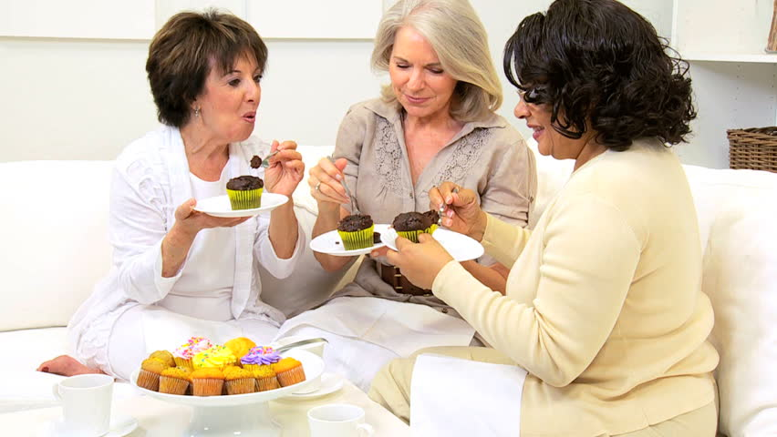 Retired multi ethnic girlfriends enjoying afternoon tea and cakes home - HD stock footage clip