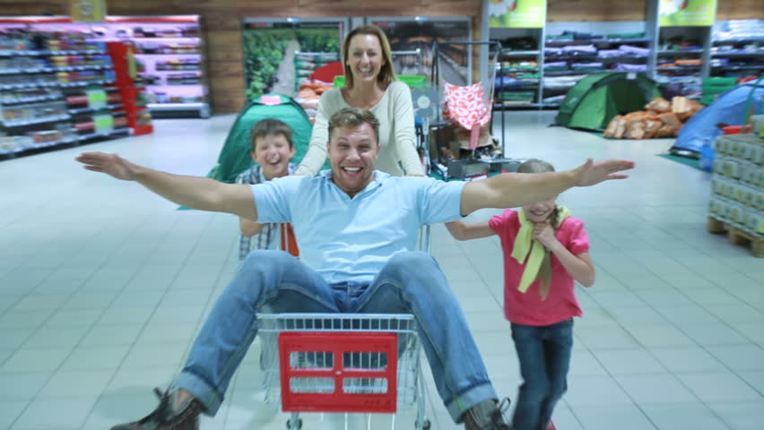 Mom and two kids having fun wheeling daddy around store in the market shopping cart.