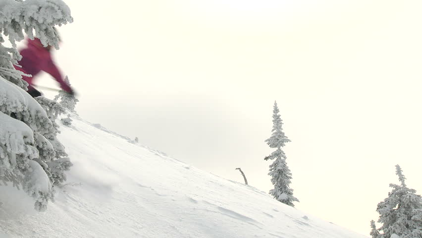 Strong female skier skis fast through some deep dry powder high in the mountains.