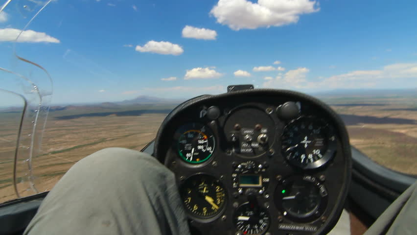 Man flies in glider above desert terrain through clear blue skies scattered with clouds. 1080p - HD stock video clip