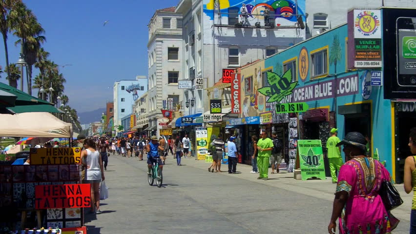 VENICE BEACH, CA - AUGUST 2: A wide shot looking down the Venice Beach Boardwalk with tourists,shops, stands, historic buildings,and a medical marijuana dispensary on in Venice Beach, CA.