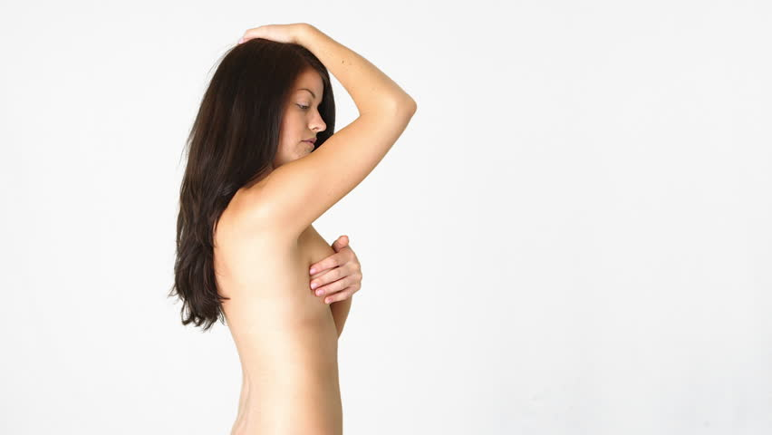 Side view of naked woman giving herself a breast exam