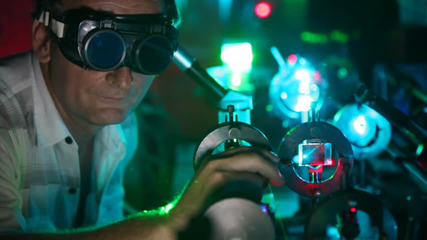 scientist in goggles twists handles of devices of laser and magnifying glasses close up