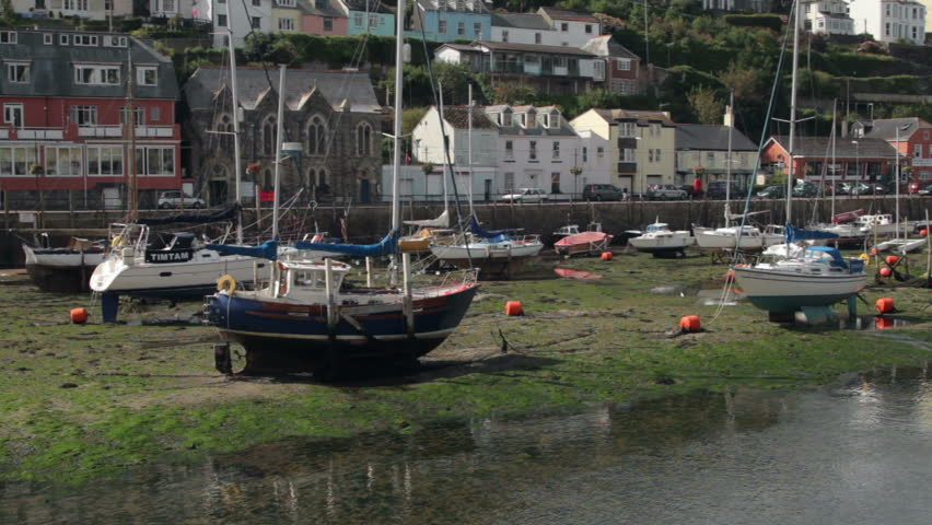 LOOE, CORNWALL/ENGLAND - SEPTEMBER 6: Yachts rest on dry land at low tide on September 6, 2012 in Looe. Looe is a picturesque Cornish fishing village and holiday destination.