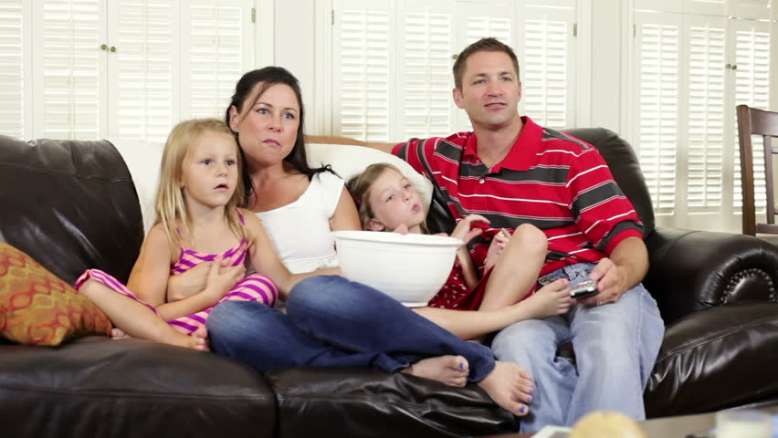 Mom and dad sit on the couch and watch TV with their two little girls. Camera dolly movement. - HD stock footage clip