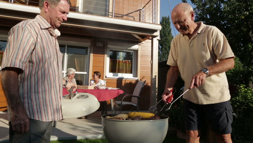 senior men cooking on kettle barbecue women sitting on terrace in garden