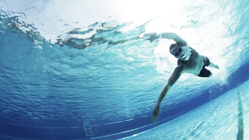 underwater view of professional crawl swimmer in outdoor swimming pool in summer