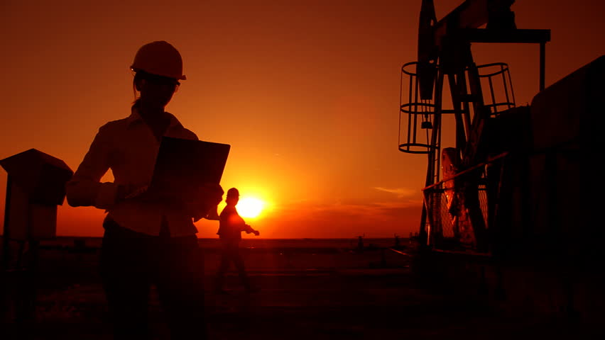 Oil pump jack and two oil workers in a field at sunset