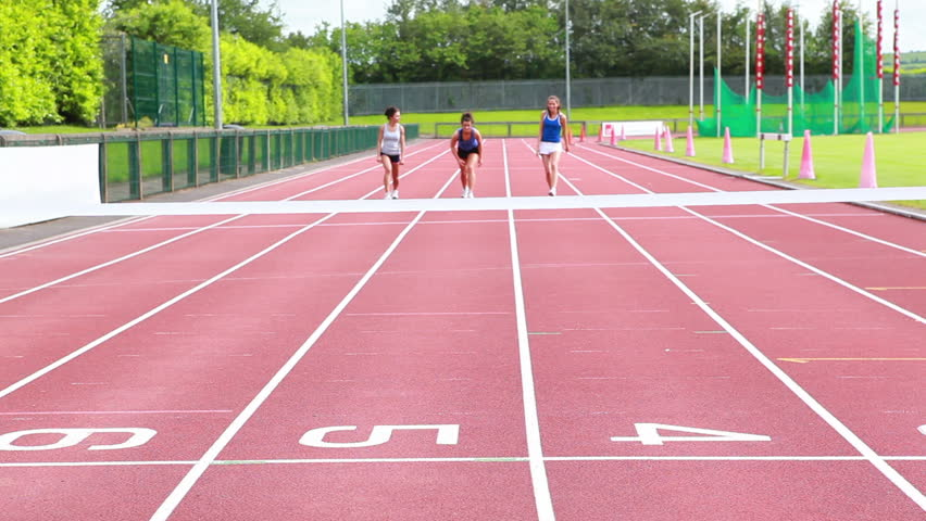 Three woman running on a track and crossing finish line in stadium