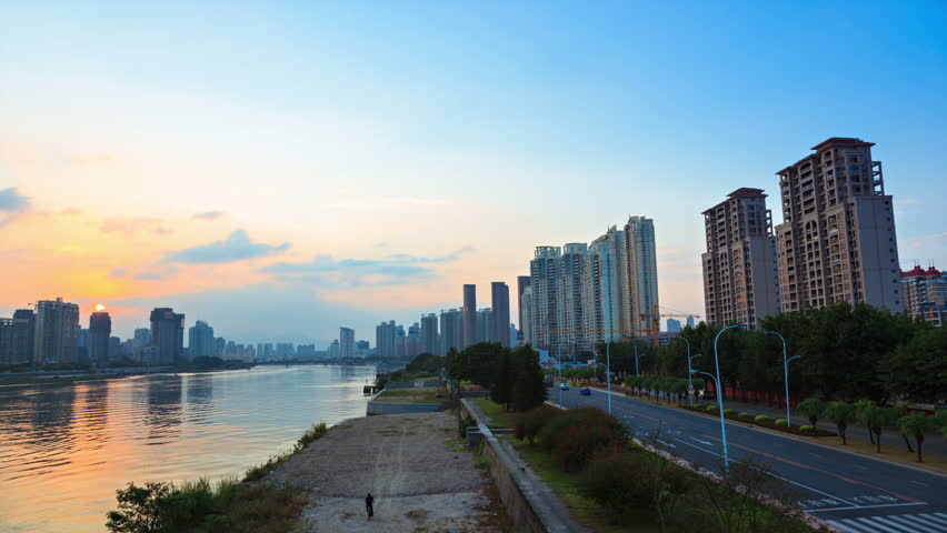 Time lapse of cityscape by the river at dusk.A dolly shot moving on a bridge from day to night.Fuzhou,Fujian,China