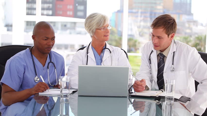 Mature doctor talking with two colleagues in a bright room - HD stock footage clip