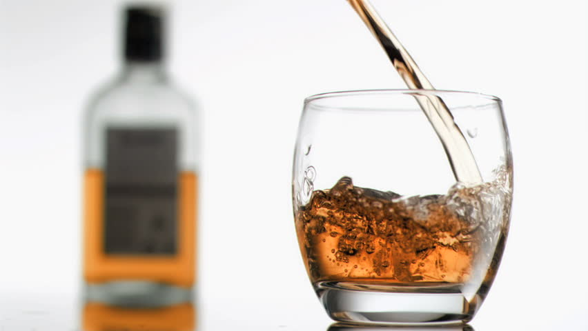 Bourbon in super slow motion filling a glass against a white background