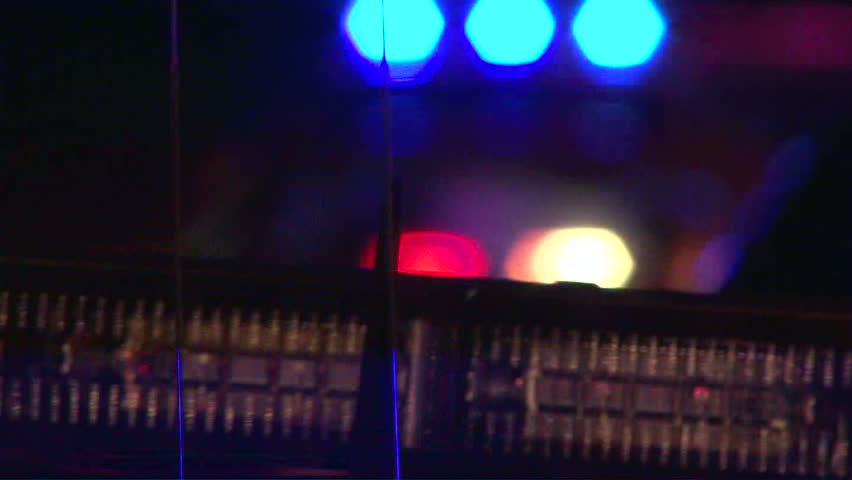 Police lights flashing at night downtown at crime scene, close up.
