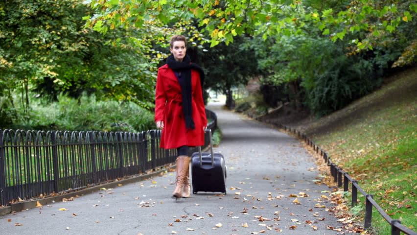 fashionable lady walking in the park with luggage
