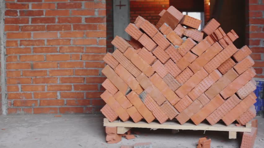 Red brick stack near wall in room at construction site, closeup view in panoramic motion - HD stock footage clip