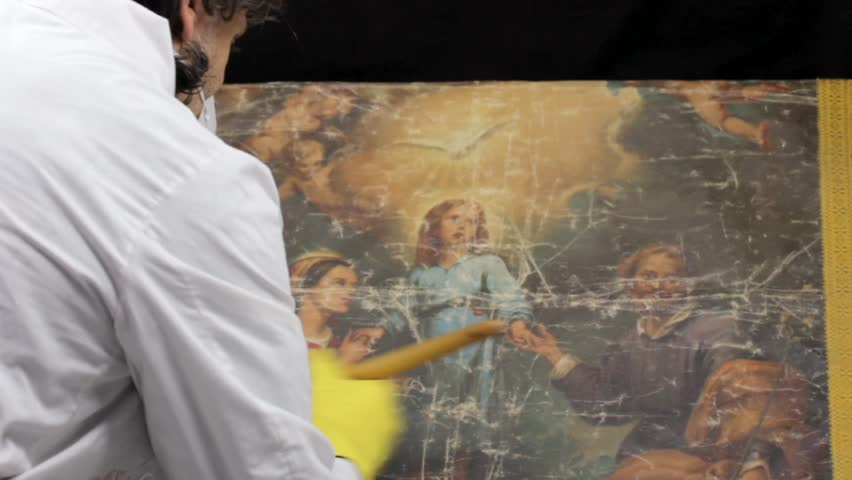 restorer at work on damaged ancient religious painting - HD stock video clip