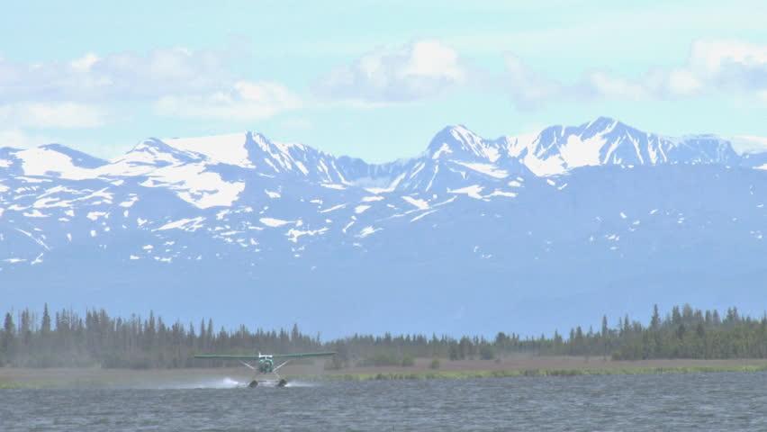 A pretty, green DeHavilland Beaver floatplane takes off from Beluga Lake in Homer, Alaska. The Kenai Mountains loom beyond. - HD stock footage clip