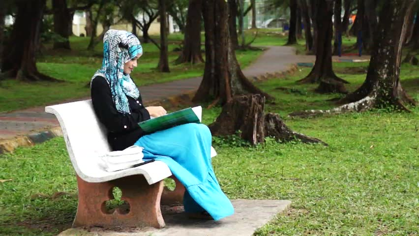 Beautiful muslim lady receive phone call while reading at the park - HD stock footage clip