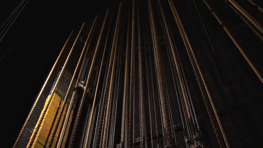 A system of ropes and pulleys backstage used to raise and lower curtains and lights. Dolly shot. - HD stock video clip