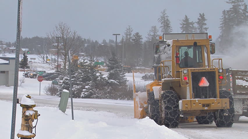 HOMER, AK CIRCA 2012: Snow blower on an excavator paired with a dump truck to clean plow piles on snowy city street.