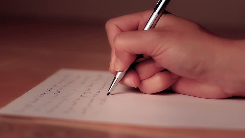 Female hand writing on a piece of paper with shallow depth of field.