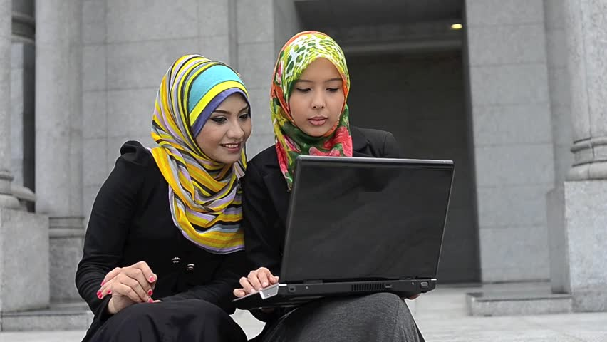 Two young pretty Asian muslim business woman in head scarf with laptop  - HD stock video clip