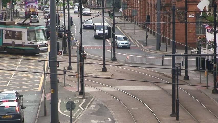 MANCHESTER, ENGLAND - CIRCA 2011: Manchester Metrolink tram crosses road.