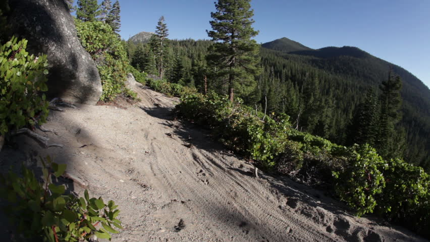 A mountain biker speeds down a dirt trail during the day, kicking up a dirt cloud, filmed at the Lake Tahoe National Park in HD with some lens flare