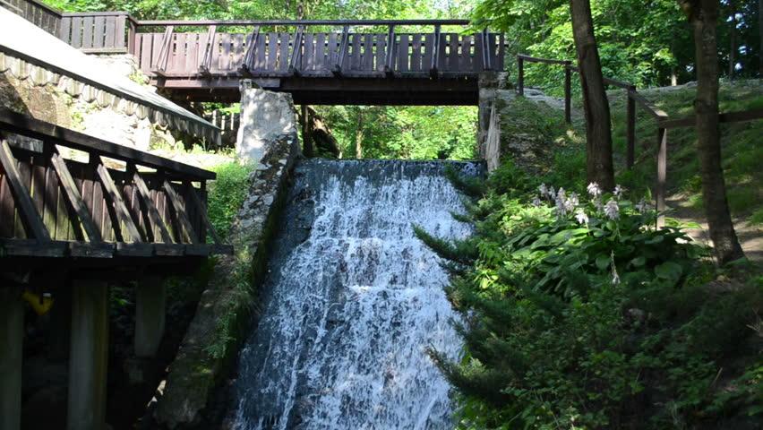 brook stream flow run through old retro water mill bridge cascade. - HD stock video clip