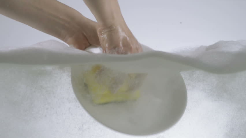 Slow Motion Shot Of Hands Washing A Ceramic Plate Using Detergent And Sponge.
