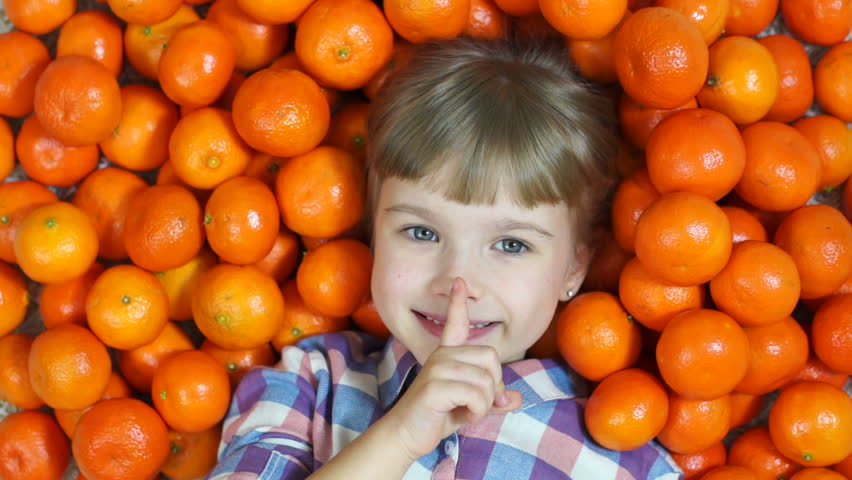 Hush hush. Happy child in oranges. Looking at camera