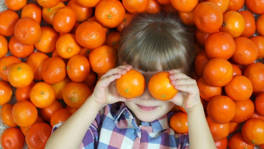 Girl orange. Happy child lying in oranges. Girl looking at camera