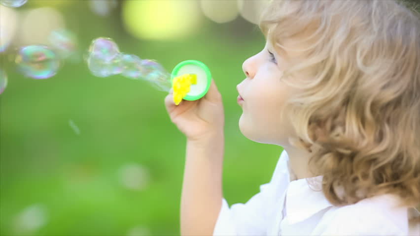 Happy Child Blowing Soap Bubbles In Spring Park. Slow
